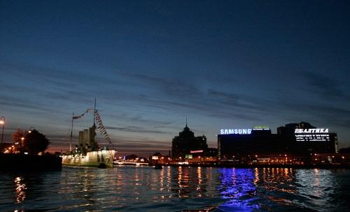The Cruiser Aurora next to billboards on the Neva.